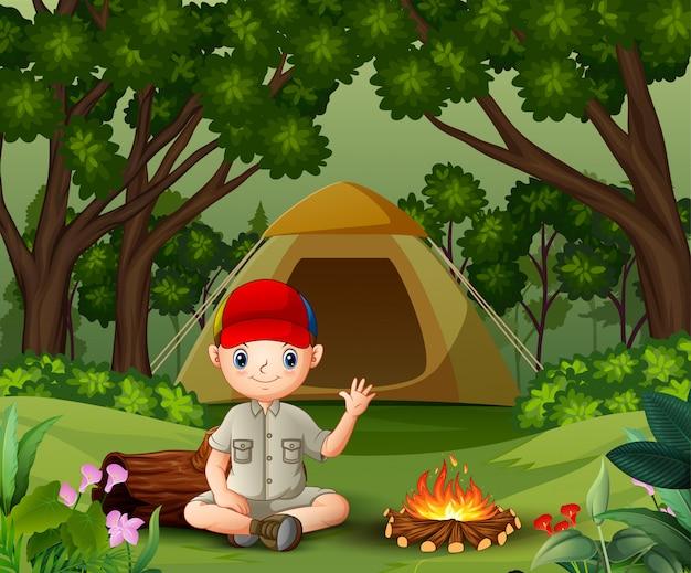 Boy scout sentado cerca de la fogata