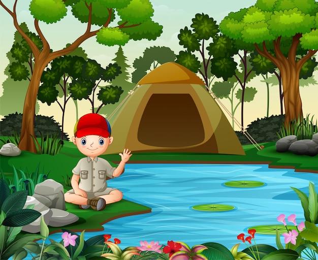 Boy scout sentado cerca del lago