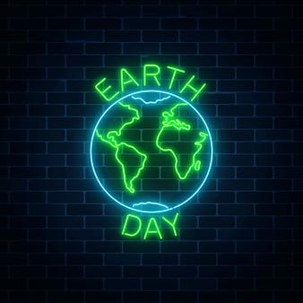 Brillante letrero de neón del día mundial de la tierra con el símbolo del globo y el texto de saludo en la pared de ladrillo oscuro