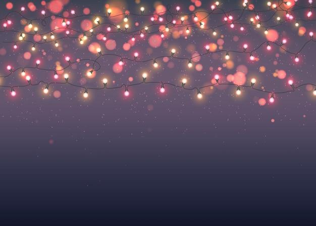 Brillantes guirnaldas de navidad sobre fondo oscuro con bokeh