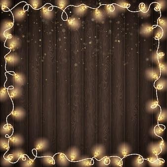 Brillantes luces de navidad. fondo de madera marrón oscuro. concepto de tarjetas de felicitación de vacaciones de año nuevo. y también incluye