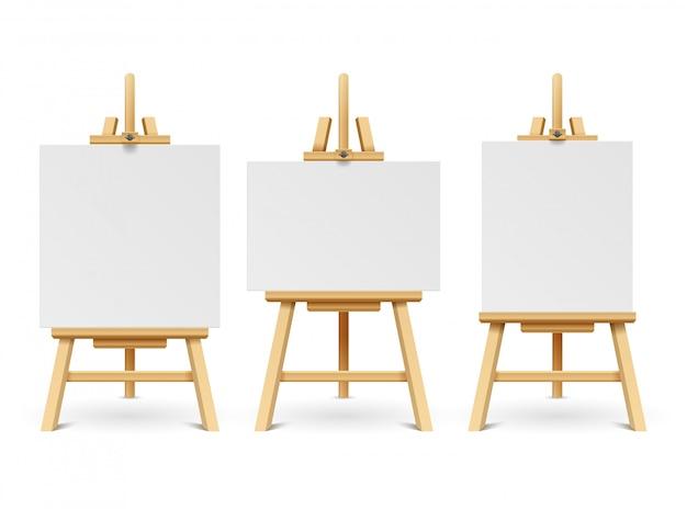 Caballetes de madera o tablas de pintura con lienzo blanco de diferentes tamaños. cartel en blanco de la obra de arte