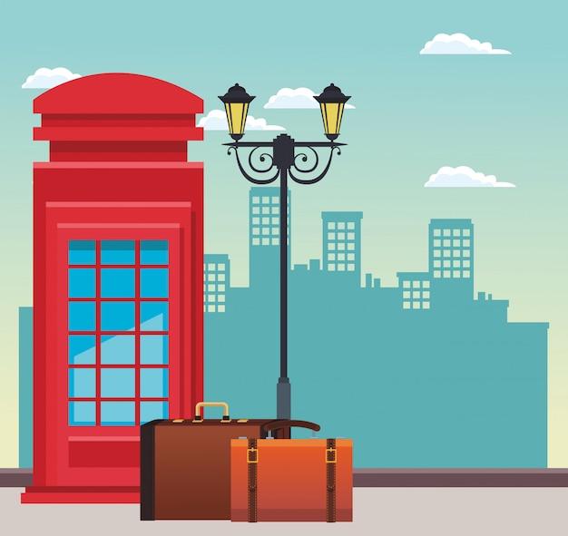 Cabina telefónica roja y farola con maletas de viaje sobre edificios urbanos de la ciudad.