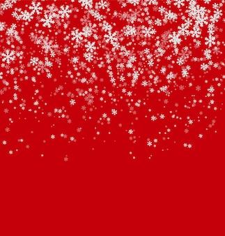 La caída de los copos de nieve blancas sobre fondo rojo.