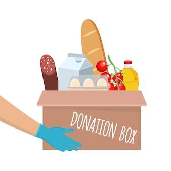 Caja de donación de alimentos con diferentes alimentos en el mismo. manos dando caja. entrega del producto durante la cuarentena.