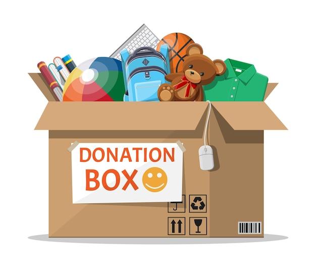 Caja de donación de cartón llena de juguetes y libros.
