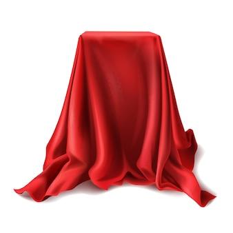 Caja realista cubierta con paño de seda rojo aislado sobre fondo blanco.