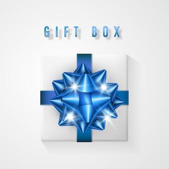Caja de regalo blanca con lazo azul y vista superior de la cinta