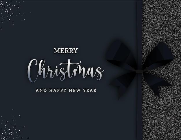 Caja de regalo de feliz navidad con lazo negro y purpurina sobre fondo oscuro