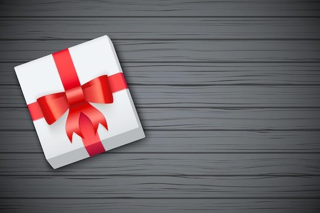 Caja de regalo en mesa de madera negra.