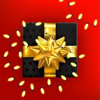 Caja de regalo de navidad con guirnalda de navidad sobre fondo rojo.