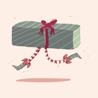 Caja de regalo de navidad con piernas de elfo aislado sobre fondo.