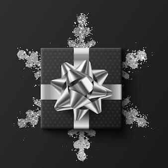 Caja de regalo negra. sobre un copo de nieve plateado. sobre un fondo oscuro. ilustración