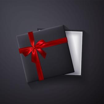 Caja de regalo vacía negra abierta con lazo rojo y cinta