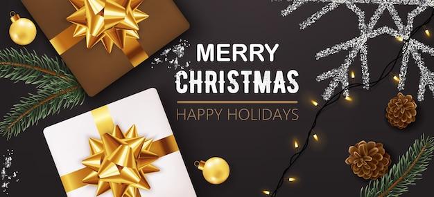 Cajas con cinta dorada rodeadas de adornos navideños