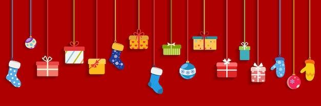 Cajas de regalo colgantes multicolores, calcetines, guantes y bolas de navidad sobre fondo rojo.