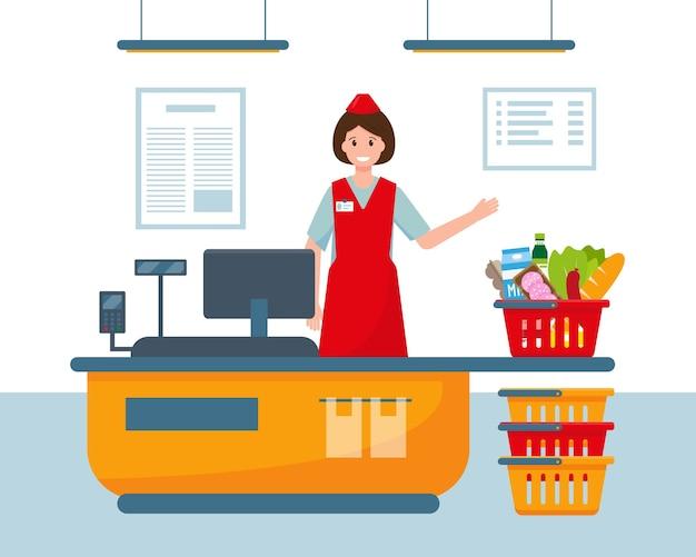 Cajera en caja registradora en supermercado y canasta llena de comida.
