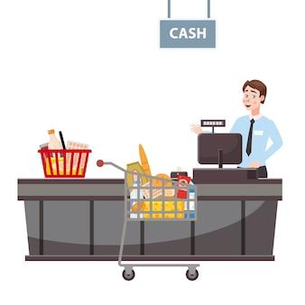 Cajero detrás del mostrador del cajero en el supermercado, tienda, tienda con una canasta llena de comestibles y un carrito lleno de comestibles.