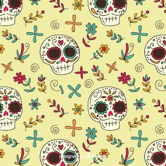 Calaveras y flores dibujadas a mano patrón día de muertos