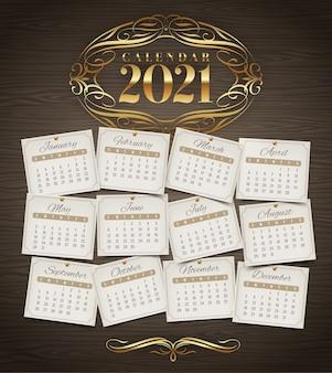 Calendario para el año 2021 con elementos de florituras doradas sobre un fondo de madera