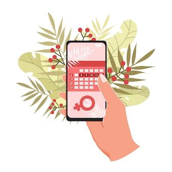 Calendario menstrual en el teléfono en mano. .
