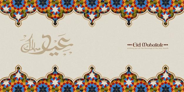 La caligrafía de eid mubarak significa felices fiestas con un colorido patrón arabesco