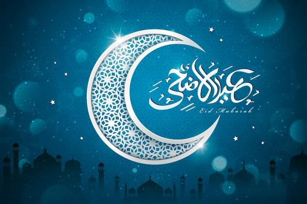 Caligrafía de saludo eid al adha con media luna tallada sobre fondo azul brillante, elementos de silueta de mezquita