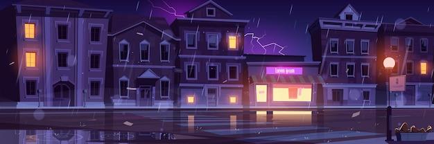 Calle de la ciudad con casas y carretera vacía en clima frío con lluvia y relámpagos.