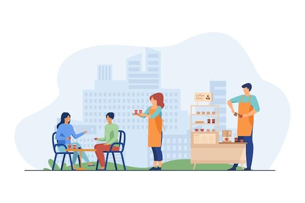 Camarera llevando café para llevar a los clientes en la cafetería al aire libre.