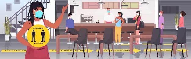 Camarera con máscara con cartel amarillo manteniendo la distancia para evitar la pandemia de coronavirus interior del café