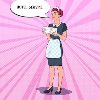 Camarera mujer sosteniendo toallas limpias