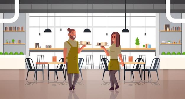 Camareros pareja llevando café y pasteles en bandeja