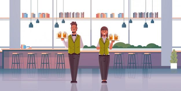 Camareros profesionales pareja sosteniendo bandejas con vasos de cerveza