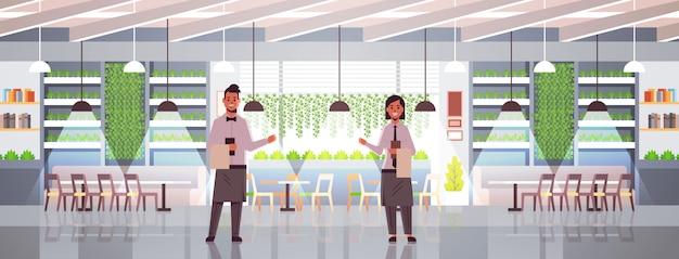 Camareros profesionales pareja sosteniendo el menú con una cálida bienvenida al acogedor restaurante