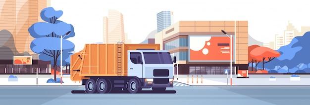 Camión de basura naranja moviéndose en la calle de la ciudad vehículo sanitario urbano