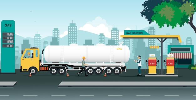 El camión está transfiriendo aceite en una estación que es inspeccionada por empleados.