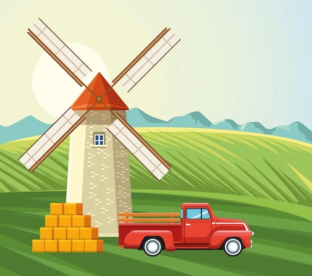 Camioneta agrícola de molino de viento y campo de heno apilado