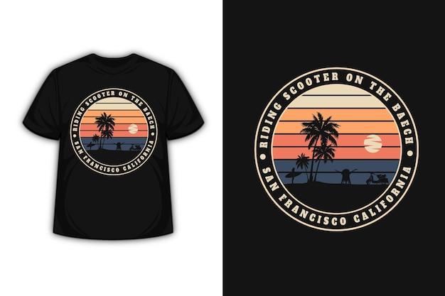Camiseta montando scooter en la playa san francisco california color crema naranja y gris oscuro