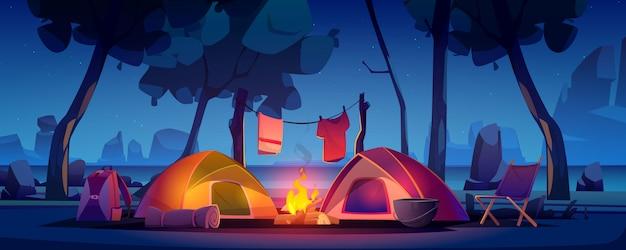 Campamento de verano con carpa, fogata y lago.