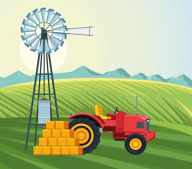 Campo de cultivo con tractor molino de viento y fardos de heno