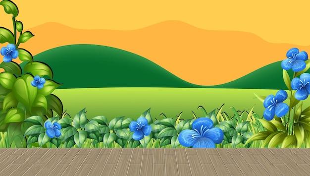 Campo de flores y pasto verde con fondo de montaña al atardecer