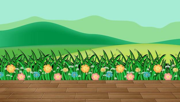 Campo de flores y pasto verde con fondo de montaña