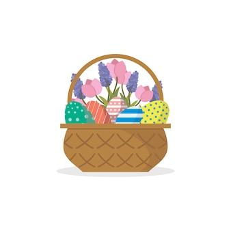 Canasta de mimbre llena de huevos de pascua pintados, tulipanes y flores lilas. vacaciones de primavera.