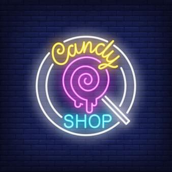 Candy shop signo de neón. piruleta pin-up en el palillo en círculo en la pared de ladrillo.