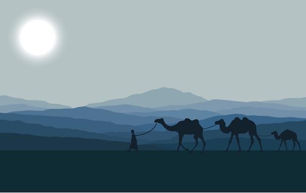 Caravana con camellos en el desierto con montañas de fondo.