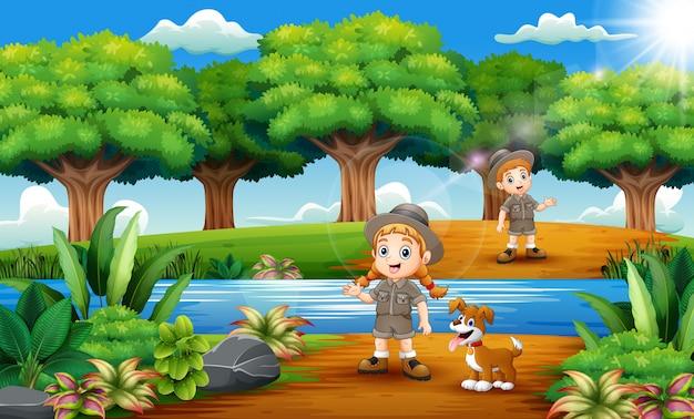 Caricatura de niño y niña zookeeper con perro en la selva