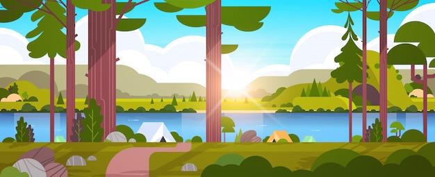 Carpas área de campamento en el bosque concepto de campamento de verano día soleado amanecer paisaje naturaleza con agua montañas y colinas