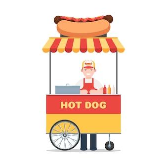 Carro de perritos calientes con el vendedor