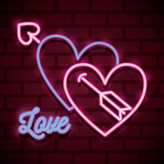 Cartel de neón del día de san valentín con texto de corazón y amor sobre muro urbano.