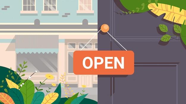 Cartel publicitario abierto colgado en la tienda de la puerta, concepto de apertura, exterior de la casa del edificio urbano
